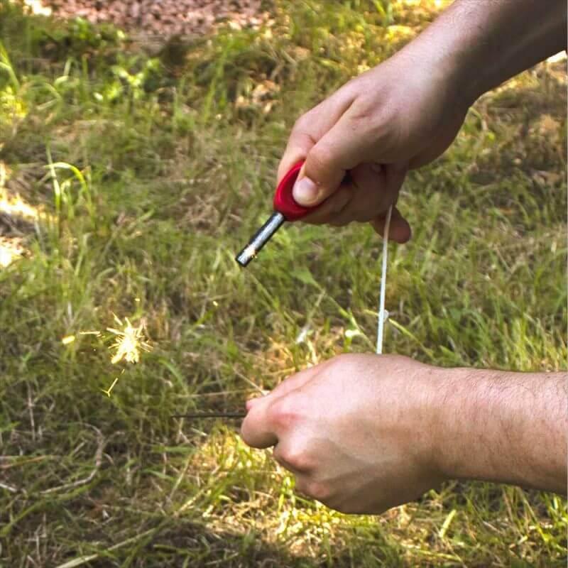En person använder Eldstål med kompass för att göra gnistor