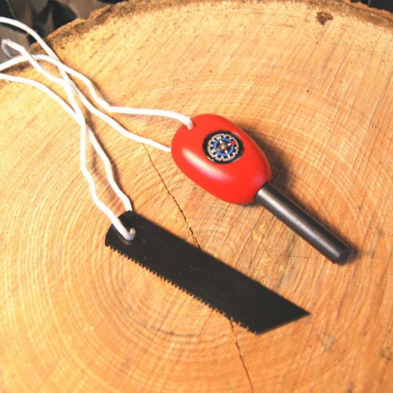 Eldstål med kompass liggandes på en stubbe