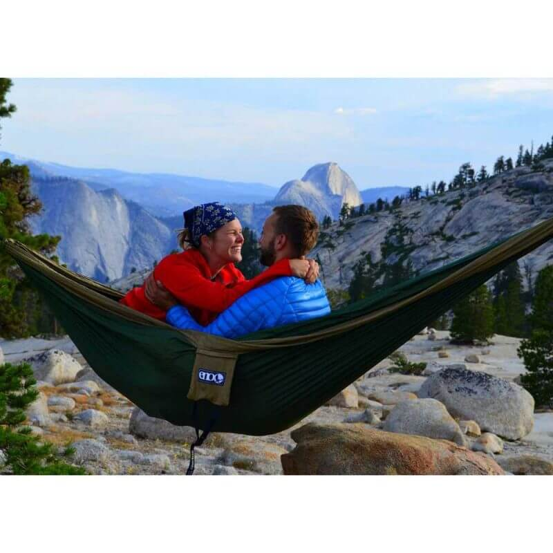 Två personer som sitter i en ENO DoubleNest Hammock –Olivfärgad