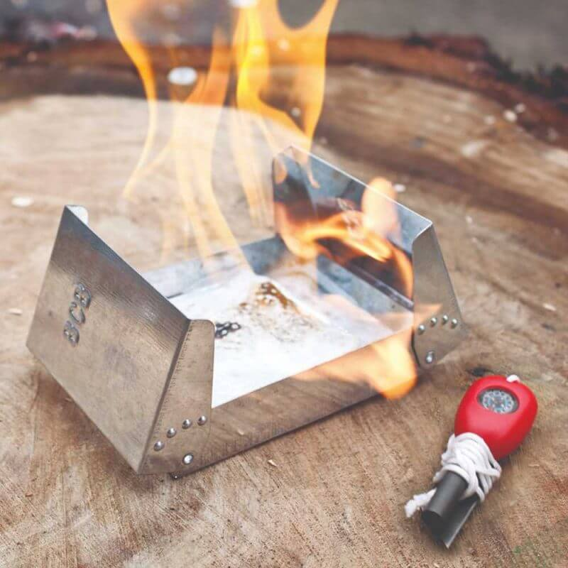 Fire Dragon nödkök med bränsle som brinner och ett tändstål bredvid