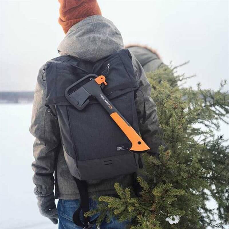Person med Fiskars Fritidsyxa XS X7 fastspänd på sin ryggsäck