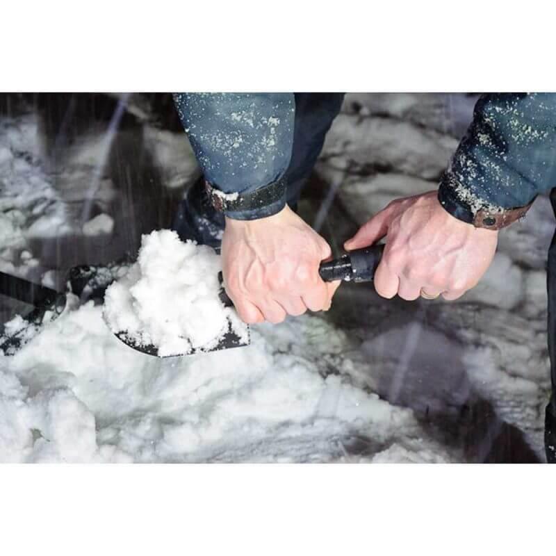 Person som skyfflar snö med Gerber Gorge Hopfällbar spade