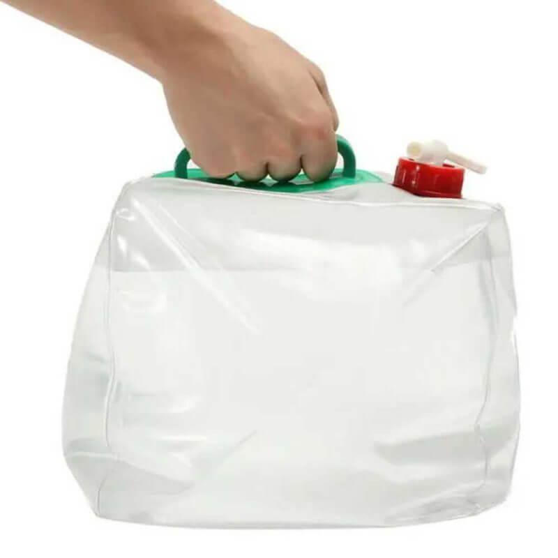 Hand som bär Hopfällbar vattendunk med tappkran 10 liter