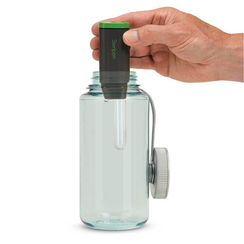 Person som använder SteriPEN Adventurer Opti –UV-lampa vattenrening i en flaska med vatten